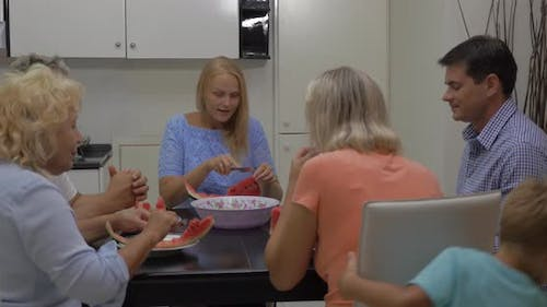 Family eating watermelon at home