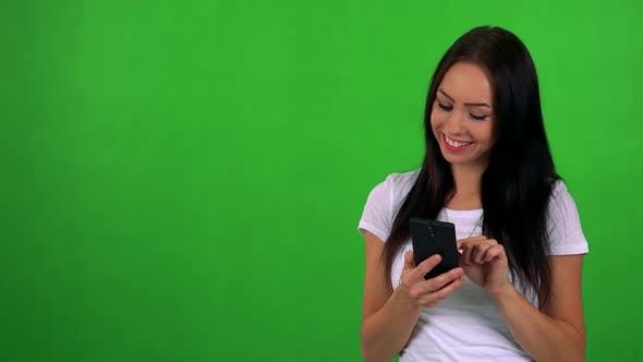 Cover Image for Young Pretty Woman Works (Typing) on Smartphone - Green Screen - Studio