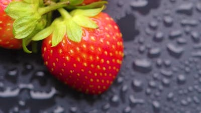 Strawberry Covered with Water Droplets are Spinning on a Wet Table