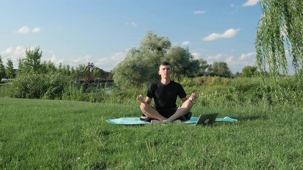 Man practicing yoga, meditating in park, sitting in lotus pose on yoga mat