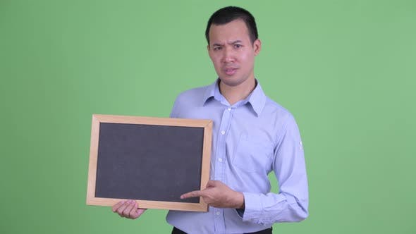 Thumbnail for Stressed Asian Businessman Holding Blackboard and Giving Thumbs Down