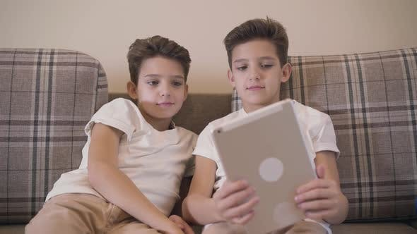 Thumbnail for Front View Close-up of Two Caucasian Twin Brothers Looking at Tablet Screen and Smiling