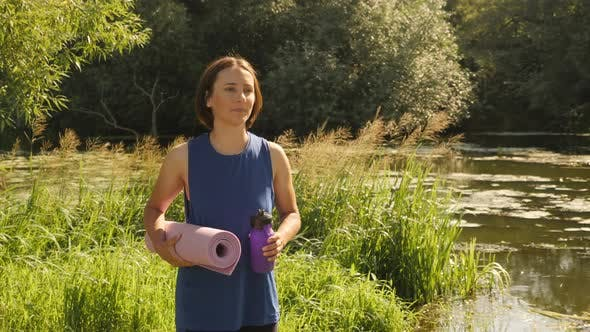 Woman walking in park after yoga class outdoors.