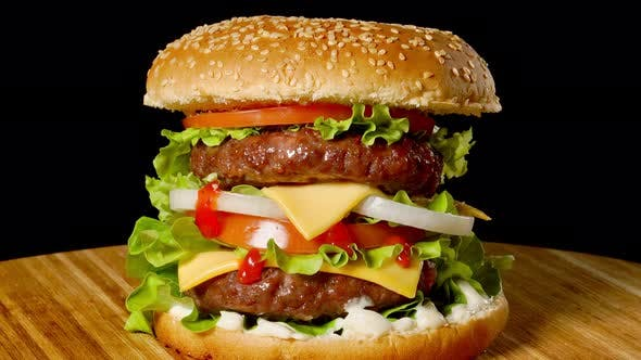 Thumbnail for Cheeseburger with Bacon on a Dark Background. Close-up. Macro Shooting.