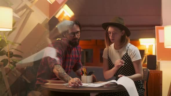 Thumbnail for Two Stylish Diverse People Are Sitting At The Table While Energetically Discussing the Project