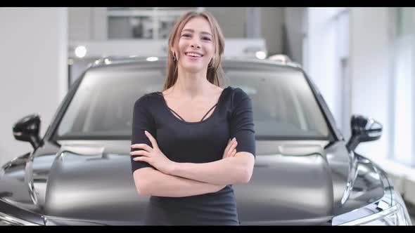 Thumbnail for Portrait of Smiling Caucasian Girl Posing in Front of New Black Automobile