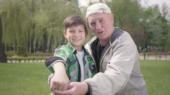 Thumbnail for Portrait of Cute Happy Little Boy in a Checkered Shirt and Positive Old Man Looking in the Camera