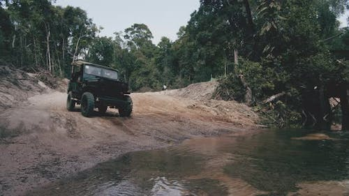 Deep Green Jeep Crossing a Shallow River