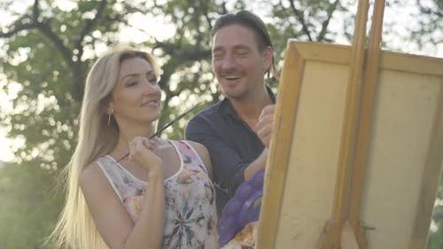 Happy Caucasian Adult Couple of Artists Painting Picture at Sunset. Portrait of Smiling Man and