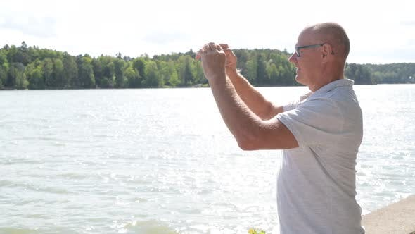 Cover Image for Happy Senior Man Recording Video With Phone By The Lake