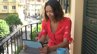 A woman reading a tablet mobile device e-reader traveling in a luxury resort town in Italy, Europe