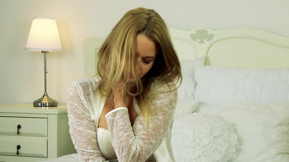 Thumbnail for A Young Attractive Woman in White Nightwear Sits on a Bed, Looks at the Camera and Plays with Hair