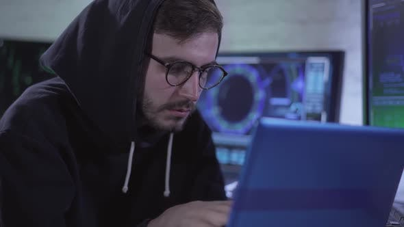 Thumbnail for Portrait of Focused Young Man Hacking Web Site or Launching Computer Virus Using Global Network
