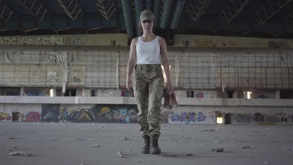 Thumbnail for Attractive Young Woman in Military Uniform Walking Slowly in Dusty Dirty Abandoned Building Carrying