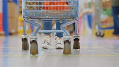 Woman is Carrying a Grocery Cart in a Supermarket