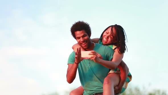 Thumbnail for Young man giving his girlfriend a piggyback ride while taking selfie