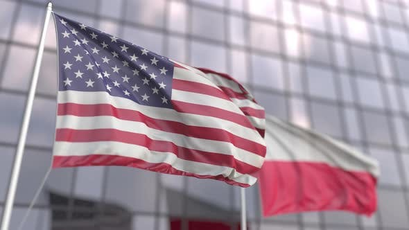 Waving Flags of the USA and Poland in Front of a Skyscraper