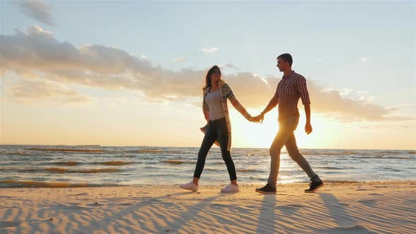 Thumbnail for A Loving Couple Walking Holding Hands. Going Along the Seashore at Sunset