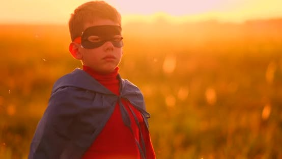 Cover Image for A Child in the Costume of a Superhero in a Red Cloak Runs Across the Green Lawn Against the Backdrop