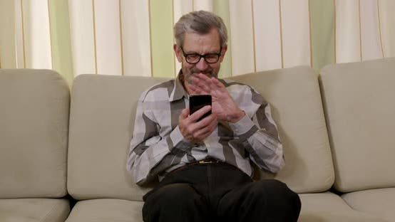 Thumbnail for Close-up. Positive Male Retiree in Eyeglasses, Talking on the Phone. Old Retiree Using Smartphone