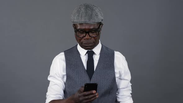 Thumbnail for Stylish African Man Texting on Smartphone
