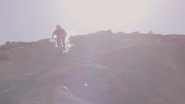 Thumbnail for Slow motion of guy riding mountain bike and skidding down hill.