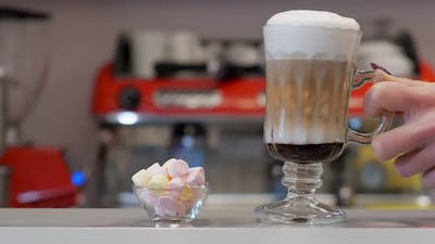 Waiter Putting Coffee Next to the Marshmallows on a Bar
