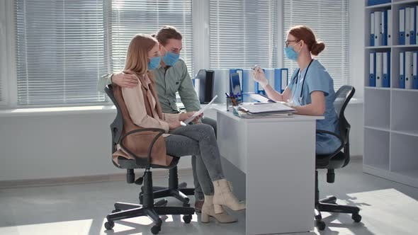 Female Doctor in Medical Mask and Gloves Gives Analysis Results to Young Married Couple Side in