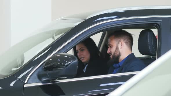 Thumbnail for A Man and a Woman Buying a New Car. Buyers Sit in the New Car Showroom