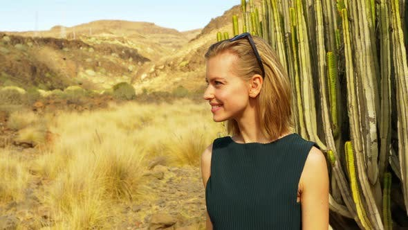 Thumbnail for Model with Cacti in Background Lip Biting and Waving at Someone