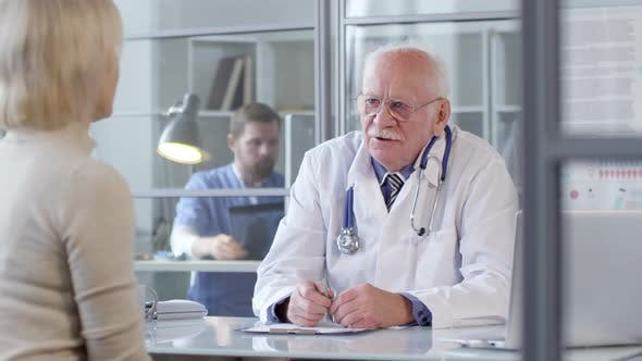 Thumbnail for Senior Doctor Speaking with Female Patient
