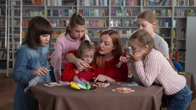 Teacher with Girls Decorating Cookies in Class