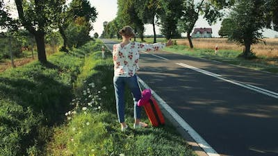 Young Woman Hitchhiking on Countryside Road