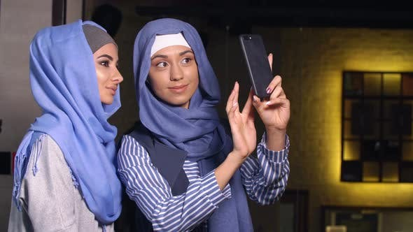 Thumbnail for Modern Muslim Women Take Pictures on a Mobile Phone. Girls in Hijabs Talking and Smiling