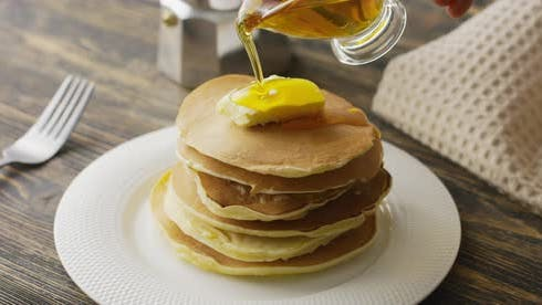 Food and Cooking Concept. Stack of Pancakes with Butter and Warm Maple Syrup in Slow Motion