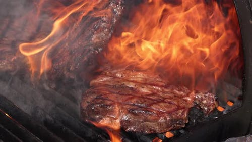 Searing and flipping ribeye steaks on grill