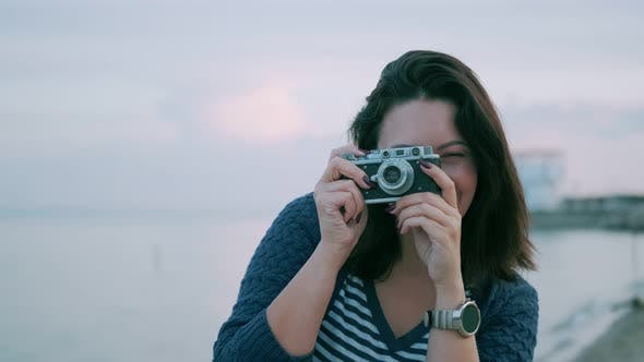 Thumbnail for Portrait of a Girl with a Retro Camera. Young Woman Takes Pictures on a Vintage Camera By the Ocean