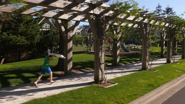 Thumbnail for Boy running through park with toy airplane