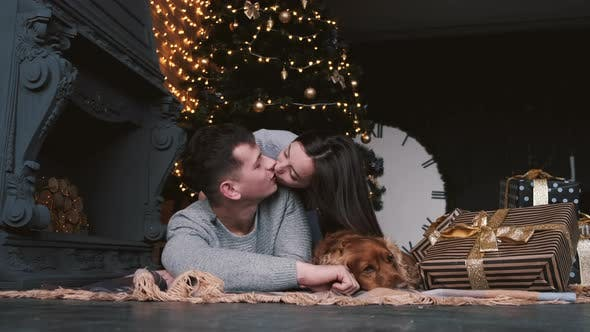 Thumbnail for Mann und Frau liegend auf dem Boden und küssen im dekorierten Zimmer
