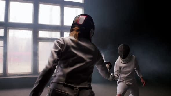 Thumbnail for Two Young Women Having a Fencing Duel in the Smoky Studio