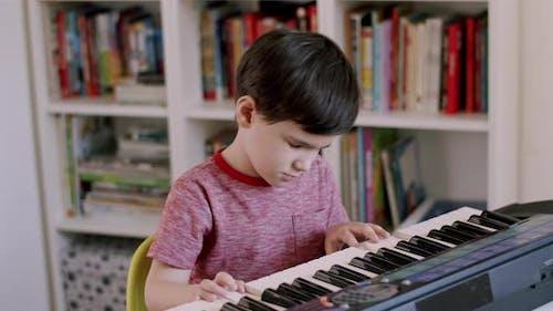 Preschooler Child Devotedly Playing on Electronic Keyboard