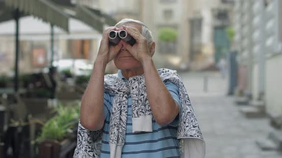 Thumbnail for Senior Man Tourist Exploring Town, Looking in Binoculars. Travel Lviv, Ukraine