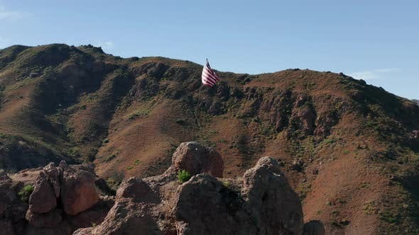 Thumbnail for Drone Flying Around the Striped Flag Set Up in the Rocky Mountain, Malibu USA