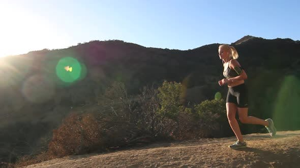 Thumbnail for A young woman runner trail running.
