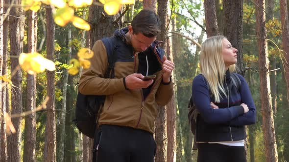 Thumbnail for A Hiking Couple Stands in a Forest, the Man Works on a Smartphone and the Woman Waits Impatiently