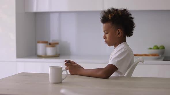 Schöner Afroamerikaner Junge benutzt Smartphone am Tisch im Wohnungsinneren Spbi