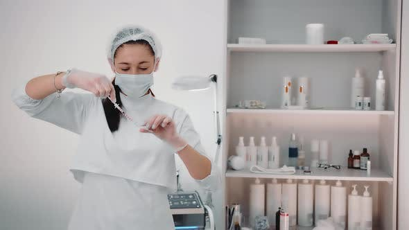 Der Cosmetologist Wählt das Medikament in die Spritze, um die Haut zu verjüngen