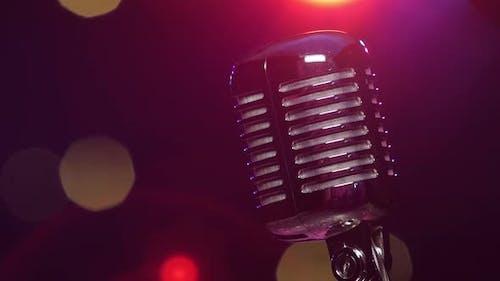 Vintage Shiny Mikrofon Reflektiert Glitzer-Konfetti gegen verschwommene Blinklicht