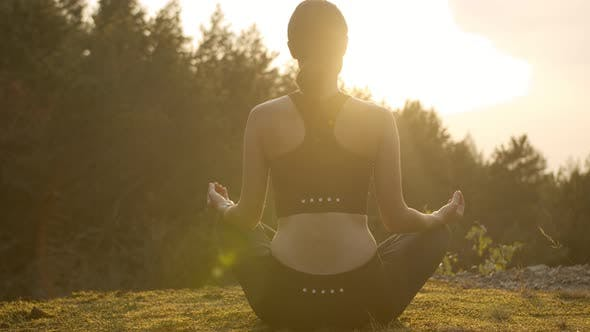 Woman Meditating on the Mountainside