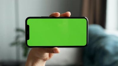 Close-Up Of A Woman's Hand Holding Horizontally A Smartphone with A Green Screen